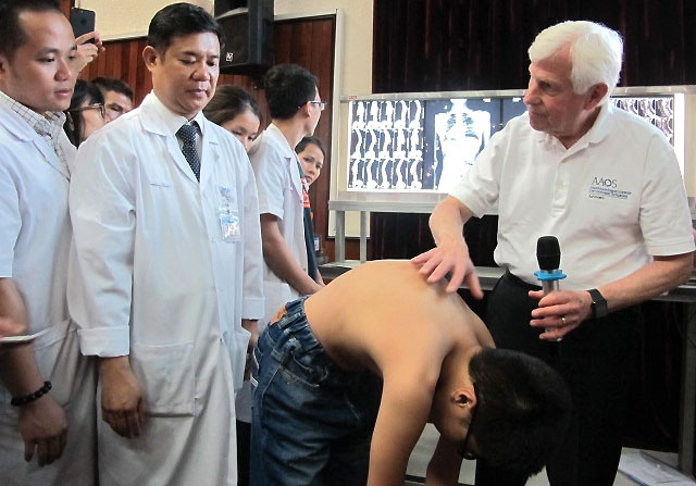 Giáo sư Stuart (bên phải), phó giao sư Sơn (thứ 2 bên trái) khám cho một trẻ bị cong vẹo cột sống. Ảnh: N.P.